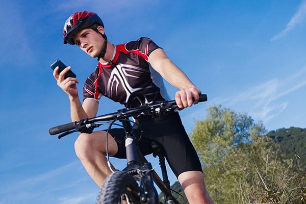 young-man-with-telephone-riding-mountain-bike